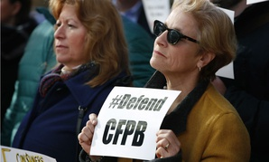 Sally Greenberg, with the National Consumers League, right, outside the Consumer Financial Protection Bureau in Washington on Nov. 27.