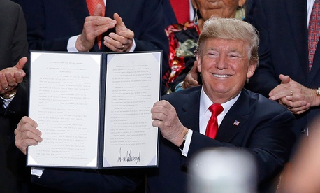 Donald Trump holds up a signed proclamation to shrink the size of Bears Ears and Grand Staircase Escalante national monuments at the Utah State Capitol on Monday.