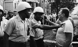 Chicago Policeman Eddie Cooper (left), places his hand on the shoulder in a restraining action of an unidentified man who protested a civil rights march in the Chicago area, Aug. 22, 1966.