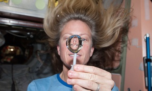 NASA astronaut Karen Nyberg, Expedition 36 flight engineer, squeezes a water bubble out of her beverage container, showing her image refracted, in the Unity node of the International Space Station in 2013.