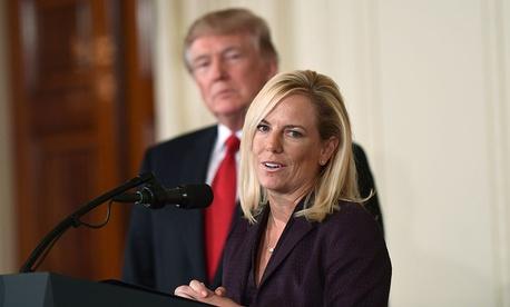 Kirstjen Nielsen speaks as Donald Trump looks on in October at the White House.