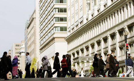 Pedestrians walk across the street at the intersection of 13th and E streets NW, in downtown Washington.
