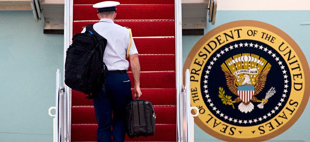 A miliary aide carries 'the football' in 2010 onto Air Force One.