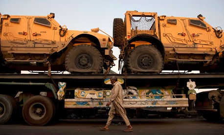 In this Nov. 26, 2013, file photo, a Pakistani man walks by a truck carrying NATO military vehicles at a terminal in Karachi, Pakistan.