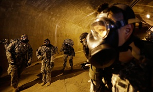 Soldiers of the U.S. Army 23rd chemical battalion wearing gas masks gather at a tunnel in 2015.