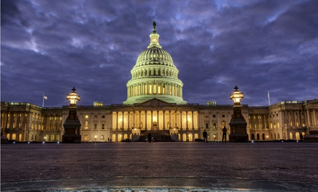 Lights shine inside the U.S. Capitol Building as night falls in Washington, Sunday, Jan. 21.