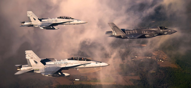 A Marine Corps F-35 Lightning II aircraft is escorted by two Marine F/A-18 Hornets.