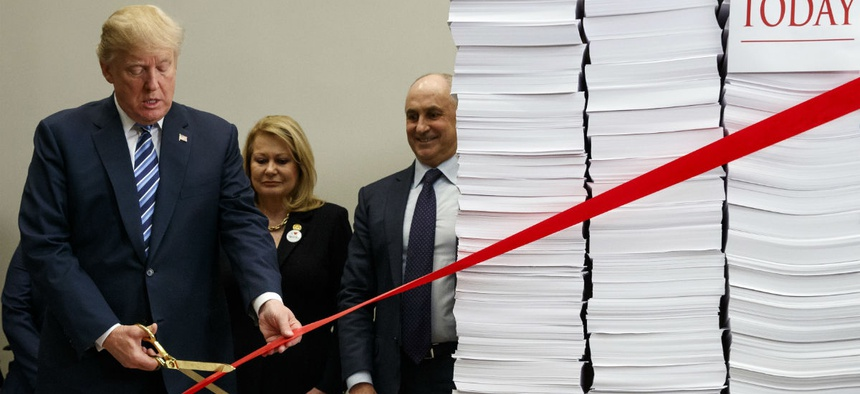 President Trump symbolically cuts red tape during a December event to tout the administration's regulatory reforms.