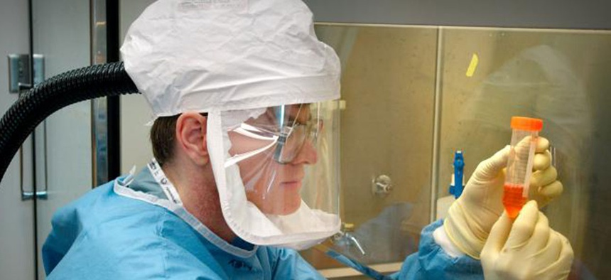 A CDC researcher examines a reconstructed 1918 pandemic flu sample in 2010.