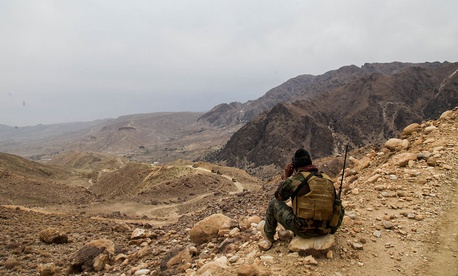 An Afghan 8th Special Operations Kandak Commando provides early warning for a convoy from a mountain top in Wach Kot Valley, Nangarhar province in December.