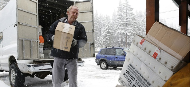 Postal worker Rex Harrison unloads his vehicle at the post office at Soda Springs, Calif., in 2016.