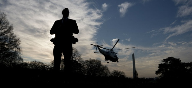 A Secret Service agent stands guard as Marine One leaves the White House. The Secret Service would see a hiring boost under Trump's budget.