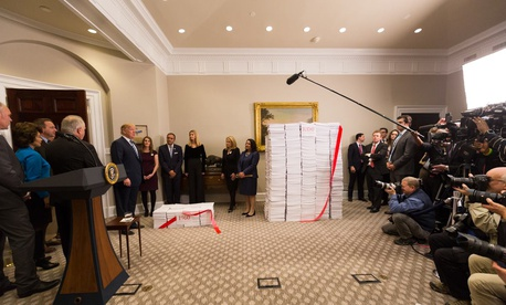 "President Trump prepares to cut the ""red tape"" of regulations during a photo op at the White House on Dec. 14, 2017."