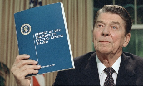 President Ronald Reagan holds up a copy of the Tower Commission report on the Iran-Contra affair, while posing for photographers after his nationally televised speech from the Oval Office on Aug. 13, 1987.