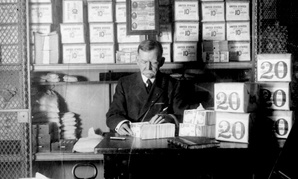 An unnamed Treasury Department official, surrounded by packages of newly minted currency, counting and wrapping dollar bills. Washington, DC 1907.