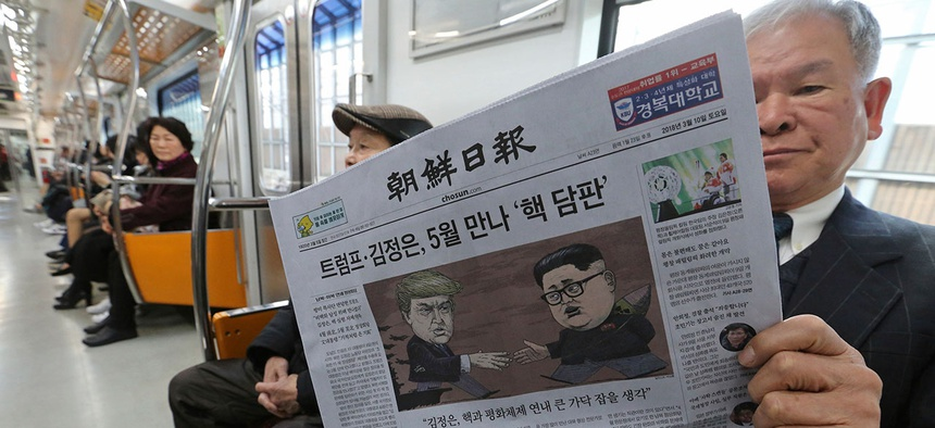 A man reads a newspaper with news of a planned summit between Kim Jong Un and Donald Trump in Seoul on March 10.