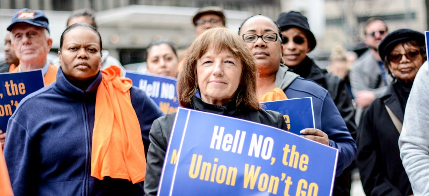 Federal union members protest the Education Department's unilateral implementation of a new collective bargaining agreement at agency headquarters in Washington on March 28.