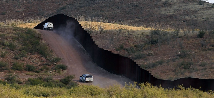 Border Patrol agents patrol near the fence in Naco, Ariz.