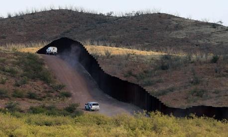 Border Patrol agents patrol near the fence in Naco, Ariz.