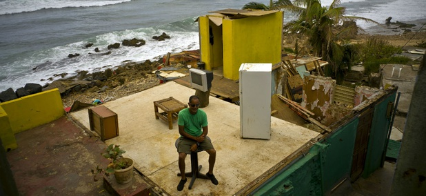 Roberto Figueroa Caballero sits on a table in his home that was destroyed by Hurricane Maria in the La Perla neighborhood on the coast of San Juan, Puerto Rico.