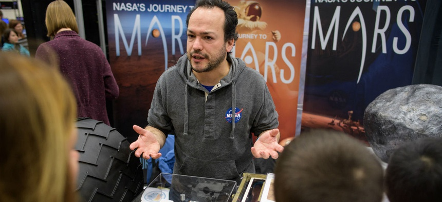 A NASA employee discusses the Mars Science Laboratory mission at the USA Science and Engineering Festival on April 6.