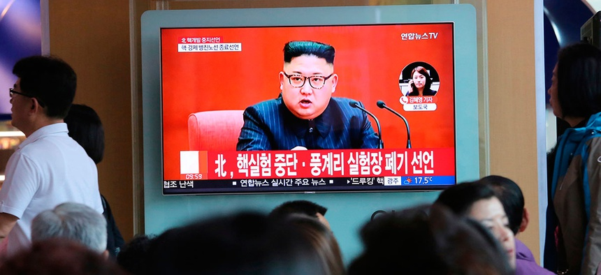 People watch a TV screen showing an image of North Korean leader Kim Jong Un during a news program at the Seoul Railway Station.