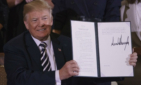Trump holds up an executive order on military spouses.