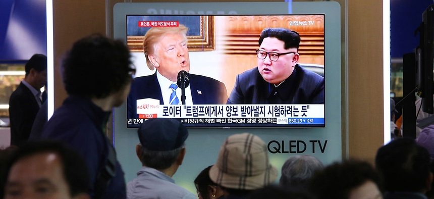 People watch a TV screen showing file footage of U.S. President Donald Trump, left, and North Korean leader Kim Jong-un in Seoul on Wednesday.