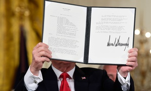 "President Donald Trump shows off a ""Space Policy Directive"" after signing it during a meeting of the National Space Council"