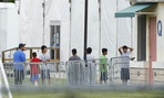 Immigrant children walk in a line outside the Homestead Temporary Shelter for Unaccompanied Children in Florida.