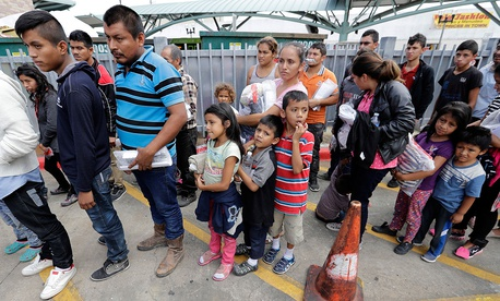 Immigrant families line up to enter the central bus station after they were processed and released by U.S. Customs and Border Protection on Sunday.
