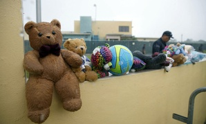 A guard walks past toys donated by protesters outside the Homestead Temporary Shelter for Unaccompanied Children in Florida.