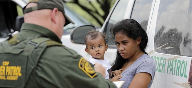 A mother migrating from Honduras holds her 1-year-old child as she surrenders to U.S. Border Patrol agents after illegally crossing the border June 25, 2018, near McAllen, Texas.