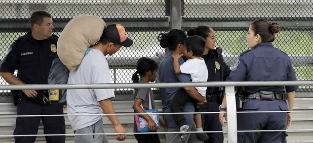 Immigrants from Honduras are escorted back across the border by U.S. Customs and Border Patrol agents on June 21, 2018, in Hildalgo, Texas.