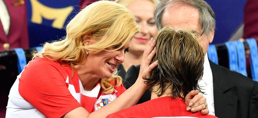 Croatian President Kolinda Grabar-Kitarović hugs Croatia's Luka Modrić after France won the final match between France and Croatia at the 2018 soccer World Cup.