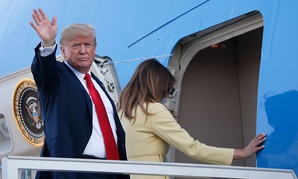 Donald Trump waves when boarding Air Force One as he leaves with his wife Melania, right, from the airport in Helsinki on Monday.
