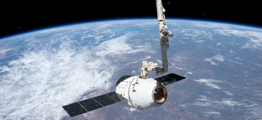 In this 2015 file photo, the Canadarm 2 reaches out to capture the SpaceX Dragon cargo spacecraft for docking to the International Space Station.