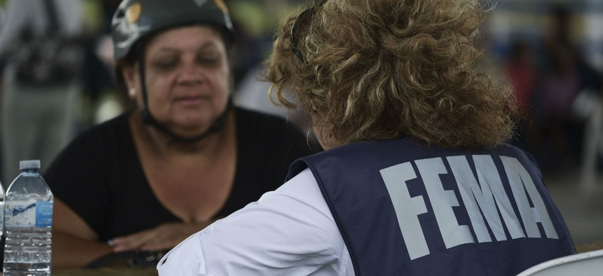 A resident meets with a FEMA representative to file forms for federal aid in the aftermath of Hurricane Maria in October 2017.