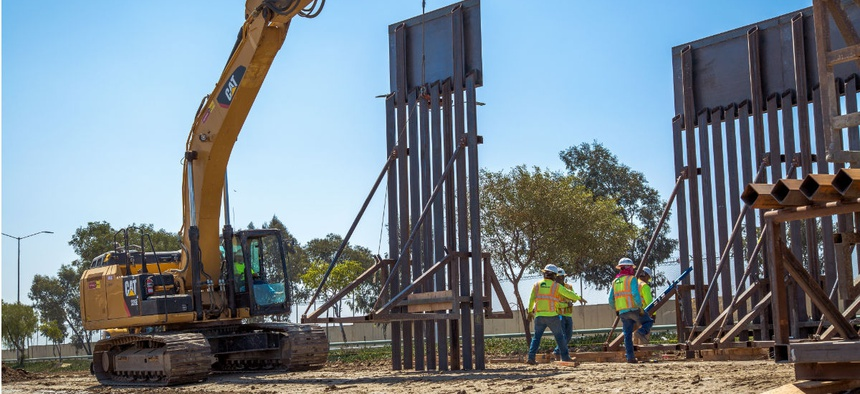 Construction workers put up a new wall panel in June at the Chula Vista Area of Responsibility, Calif.