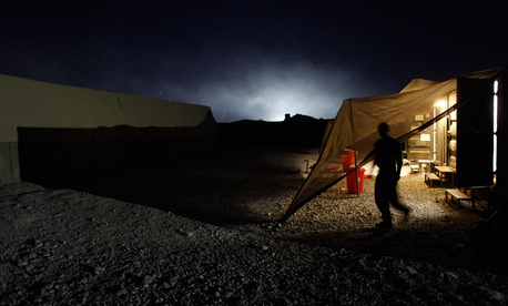 A U.S. Marine exits a steel container, the lights illuminating the smoke from a trash-burning pit, at Forward Operating Base Jackson, in Sangin, Helmand province, Afghanistan in 2002.