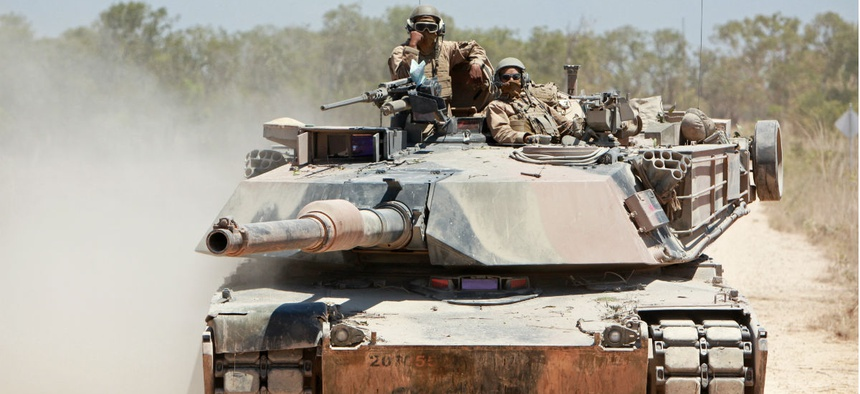 U.S. Marines with Alpha Company, 1st Tank Battalion, 1st Marine Division ride in an M1A1 Abrams tank during an exercise in 2013.
