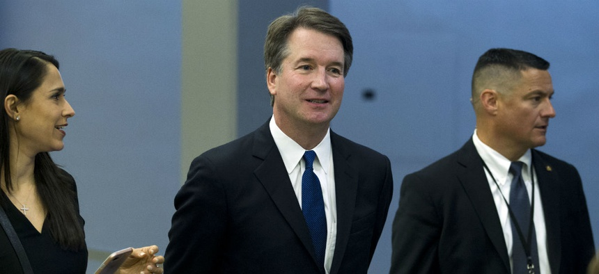 Supreme Court nominee Brett Kavanaugh (center) heads to a meeting on Capitol Hill.