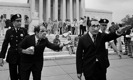 Two demonstrators, one, left, wearing a President Nixon mask and the other wearing a Secretary of State Henry Kissinger mask and giving a Nazi salute, are escorted by police from in front of the Supreme Court building in Washington, July 24, 1974.