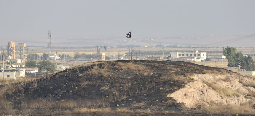 An ISIS flag sits on a hill in Syria in 2015.