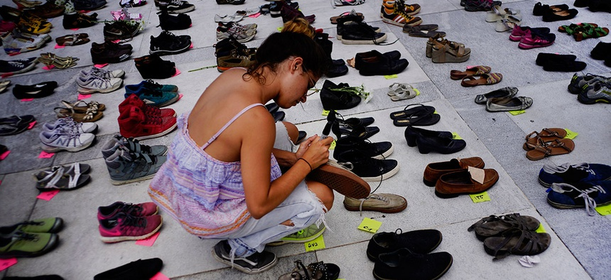 A woman places one of the hundreds of shoes in memory of those killed by Hurricane Maria in front of the Puerto Rico Capitol, in San Juan on June 1, 2018.