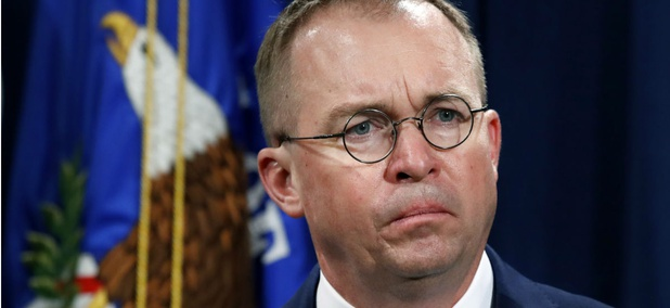 Acting CFPB Director Mick Mulvaney listens during a Justice Department news conference in July about fraud.