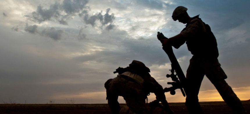 A coalition member hangs an 81-millimeter mortar prior to launching it at a known ISIS location near the Iraqi-Syrian border in May.