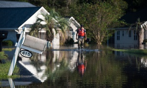 A Coast Guard member assigned to the Atlantic Strike Team walks through a flooded neighborhood in Longs, South Carolina, on Sept. 20.