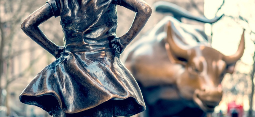 """""""The Fearless Girl"""" statue facing Charging Bull in Lower Manhattan, New York City."""