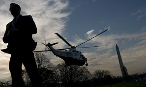A Secret Service agent stands guard as Marine One departs the White House with President Trump aboard last winter.